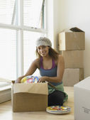 Young woman unpacking dishes — Stock Photo
