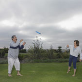 Mature couple playing Frisbee — Stock Photo
