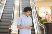 African teenage boy looking at cell phone — Stock Photo