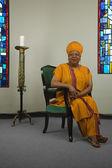 Afrikaanse vrouw zat naast kaars en gebrandschilderd glas windows — Stockfoto