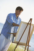 Man painting on easel outdoors — Stock Photo