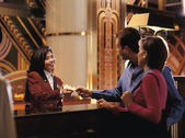 Female receptionist giving room key to couple — Foto Stock