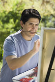 Man painting with easel outdoors — Foto de Stock