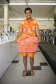Portrait of man standing in laundromat with laundry — Stock Photo