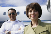 Businesswoman and male pilot standing in front of private airplane — Stock Photo