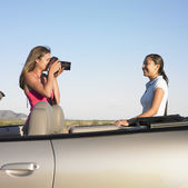 Woman taking picture of friend in convertible — Stock Photo