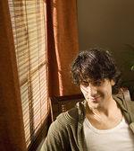 Człowiek siedzący obok okna uśmiechający się — Zdjęcie stockowe