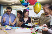 Serving cake at office birthday party — Stock Photo