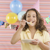 Young girl eating cake at birthday party — Stock Photo