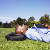 African businessman laying in grass — Stock Photo
