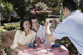 Waiter taking photograph of couple at table — Stockfoto