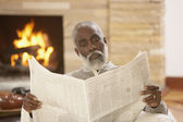 Senior African man reading a newspaper — Stock Photo