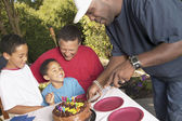 Man cutting birthday cake with family — Stock Photo