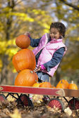 African girl trying to stack pumpkins — Stock Photo