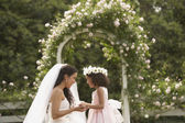 Hispanic bride and young girl smiling at each other — Stock Photo