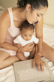 Mother holding baby and typing on laptop — Stock Photo