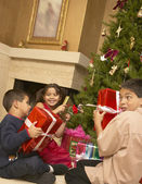 Hispanic siblings shaking Christmas gifts — Stock Photo