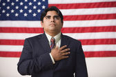 Businessman standing in front of an American flag with one hand across his heart — Stockfoto
