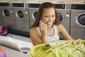 Woman talking on phone with basket of laundry in laundromat — Stock Photo
