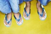Girls feet wearing flip flops — Stock Photo