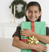 Hispanic girl holding gift and smiling — Stock Photo