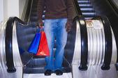 Afrikaner auf rolltreppe mit einkaufstüten — Stockfoto