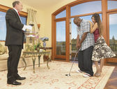 Couple playing golf in house with servant watching — Stock Photo