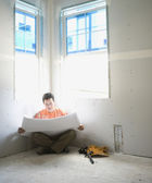 Male carpenter looking at blueprints inside construction site — Stock Photo