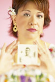 Portrait of woman holding old photograph — Stock Photo