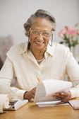 Senior African woman paying bills at table — Stock Photo