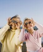 Mormor och barnbarn håller upp stenar till ögon på stranden — Stockfoto