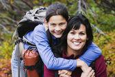 Madre e hija sonriendo juntos al aire libre — Foto de Stock