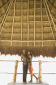 Couple standing underneath thatch roof — Stok fotoğraf