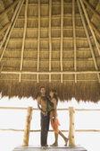çift ayakta saz çatı altında — Stockfoto