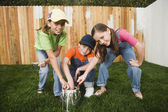 Mixed Race children painting fence — Stock Photo