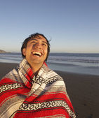 Portrait of man wrapped in blanket laughing at beach — Stock Photo