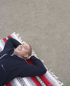 Man laying on blanket at beach with hands behind head — Stock Photo