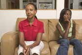 Mother and teenage daughter sitting on couch — Stock Photo
