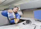 Asian businessman spilling coffee on desk — Stock Photo
