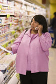 Woman on cell phone with grocery list in store — Stock Photo