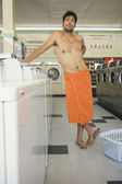 Man wrapped in towel standing in laundromat — Stock Photo