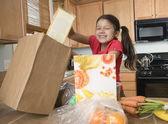 Hispanic girl unpacking groceries in kitchen — Stock Photo