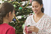 Mother opening her daughter's gift on Christmas day — Stock Photo