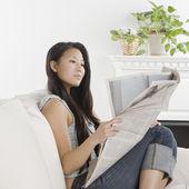 Giovane donna asiatica, leggendo il giornale sul divano — Foto Stock