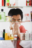 Asian man blowing nose — Stock Photo