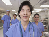 Asian female doctor smiling with co-workers in background — Stock Photo