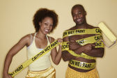 Portrait of woman wrapping man in caution tape — Stock Photo