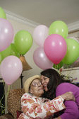 Woman hugging elderly woman with balloons behind them — Stock Photo