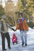 African couple pulling child on sled — Stock Photo