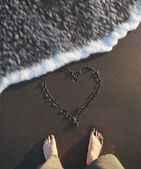 High angle view of man's feet with heart drawn in the sand at beach — Stock Photo